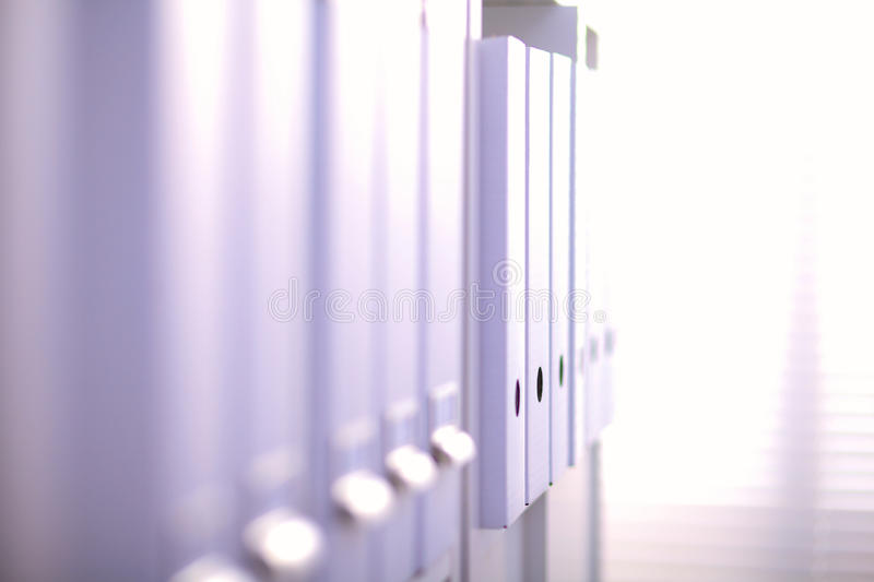 File folders, standing on shelves in the background.  royalty free stock photography