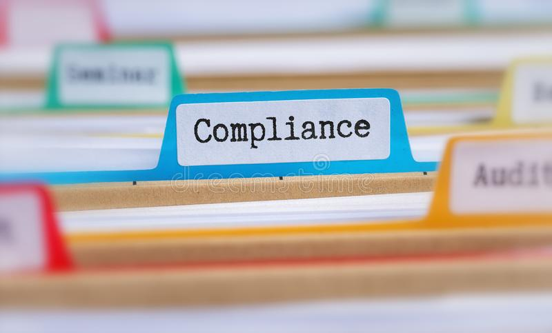 File folders with a tab labeled Compliance royalty free stock photography