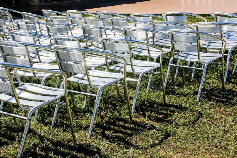 File simmetriche delle sedie pieghevoli d'argento pronte per il partito o la rappresentazione, presentazione sedie metalliche nel immagine stock libera da diritti