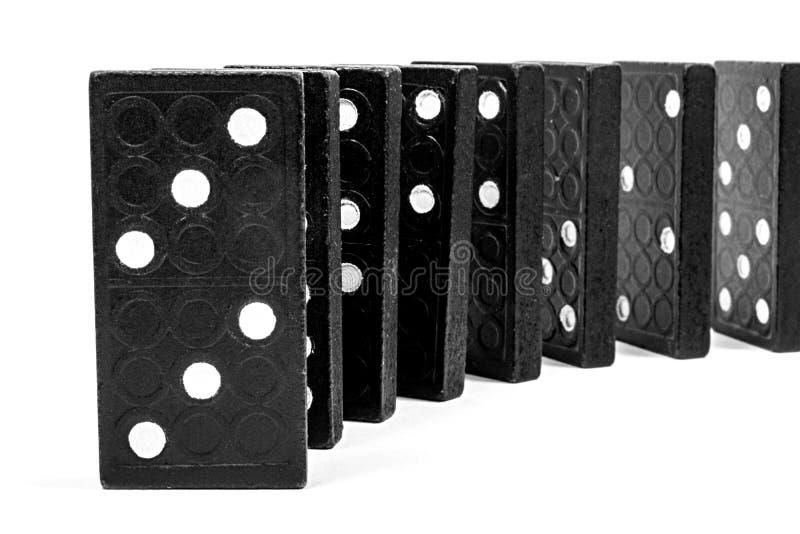 Fileira curvada dos dominós de madeira pretos que estão em um fundo branco Jogo lógico Conceito do negócio fotos de stock