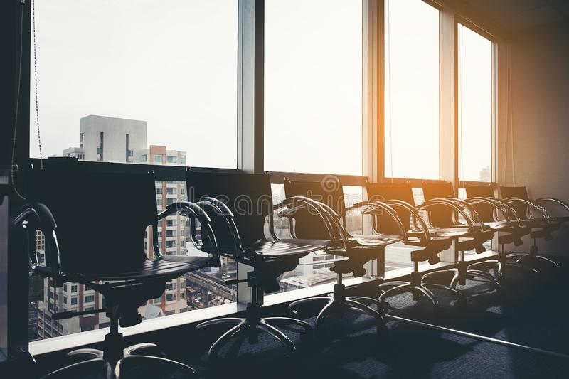 Fileira da cadeira preta moderna no espaço de escritórios vazio com grande arquitetura da cidade da opinião da janela, processo d fotografia de stock royalty free