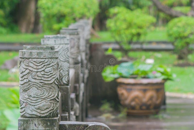 Fileira da coluna chinesa da cerca no pagode e no jardim chineses com fundo natural verde no parque público foto de stock