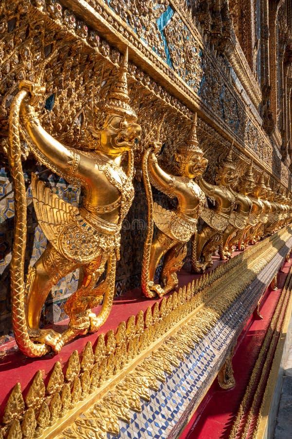 Fileira da estátua dourada de Garuda na parede bonita no templo real de Tailândia foto de stock royalty free