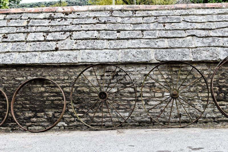 A fileira da exploração agrícola velha roda a inclinação contra uma construção de pedra velha rústica imagem de stock royalty free
