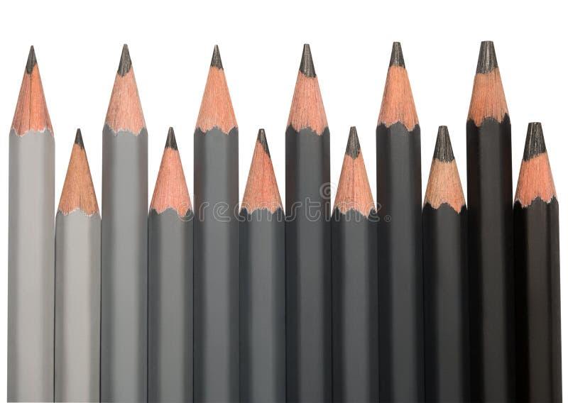 A fileira da grafite preta escreve com dureza diferente imagem de stock