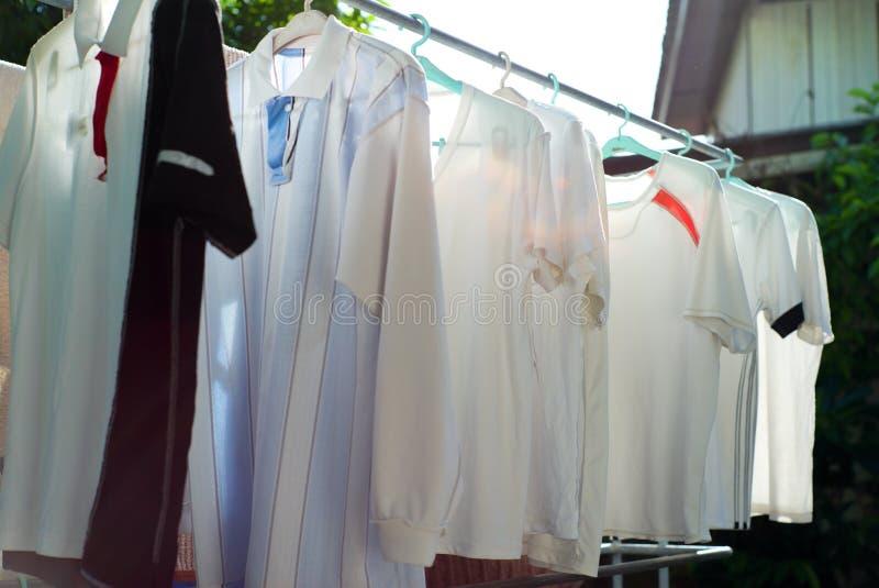 Fileira da roupa molhada que pendura na cremalheira de aço para secar usando o calor da luz solar na maneira tradicional fotografia de stock royalty free