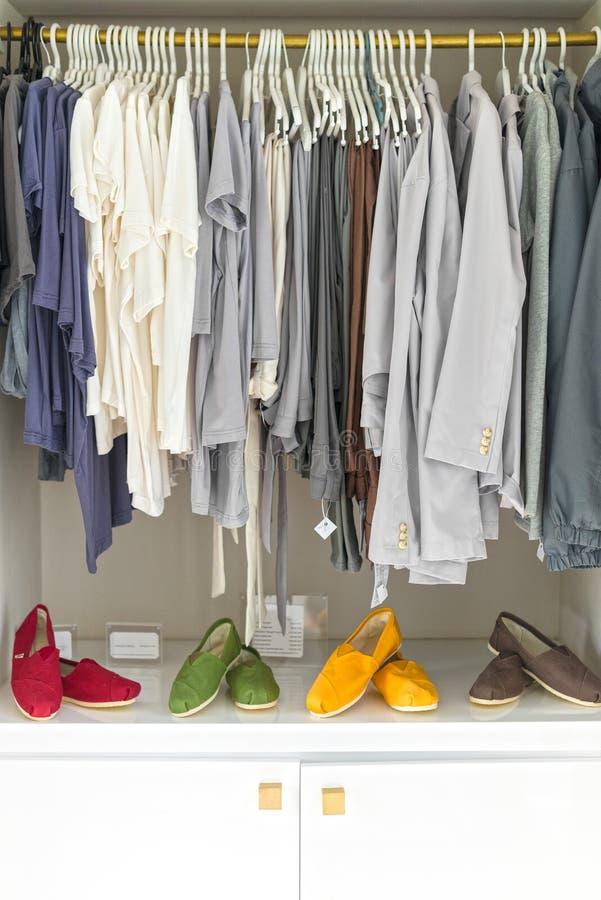 Roupa ocasional em ganchos e em sapatas na loja. fotografia de stock royalty free