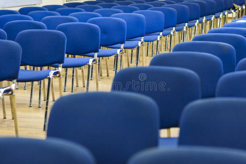 Fileira das cadeiras modernas que estão na linha no auditório vazio foto de stock royalty free