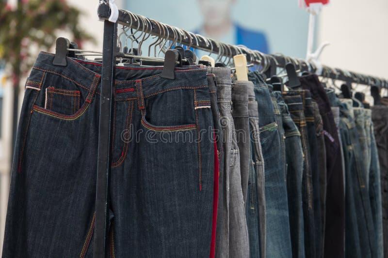 Fileira das calças de brim e da calças em ganchos para a venda fotos de stock royalty free