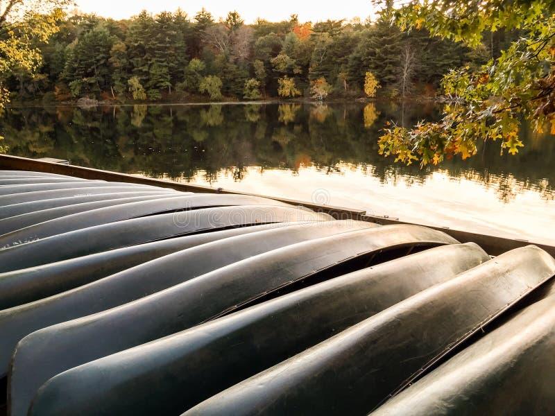 Fileira das canoas alugado viradas ao longo das proximidades do lago foto de stock