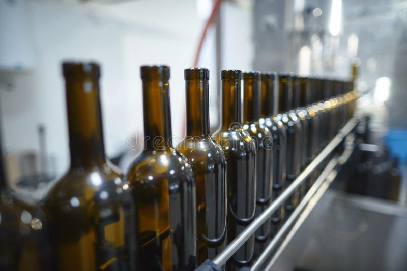 Fileira das garrafas de vinho de vidro que movem-se pelo transporte imagens de stock