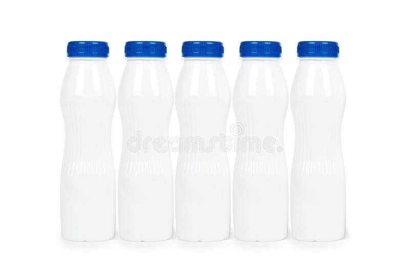 Fileira das garrafas plásticas brancas com iogurte ou leite da bebida Isolado no fundo branco Molde da mercadoria do recipiente imagens de stock