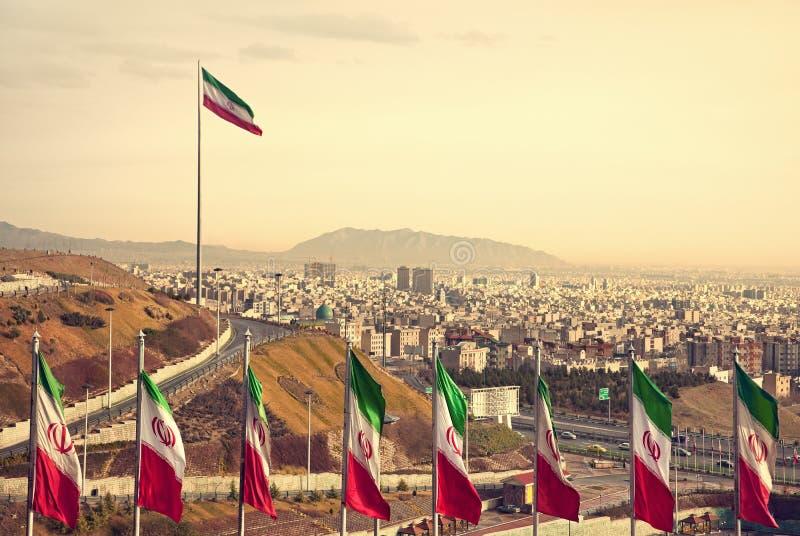 Fileira de bandeiras de Irã na frente da skyline de Tehran imagem de stock royalty free