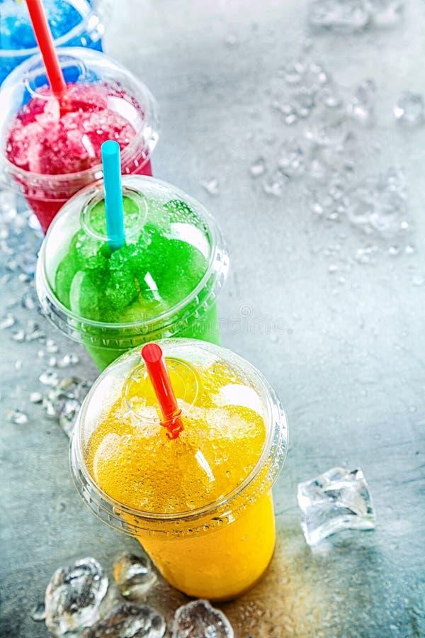 Fileira de bebidas coloridas da lama em uns copos plásticos foto de stock royalty free