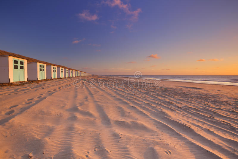 Fileira de cabanas da praia no por do sol, Texel, os Países Baixos imagem de stock