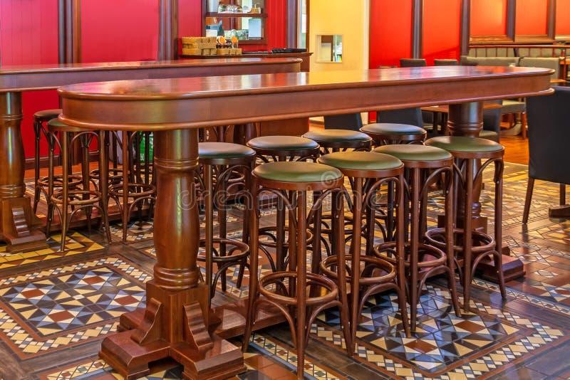 Fileira de cadeiras altas de madeira em uma barra na frente de uma tabela em um bar imagem de stock royalty free