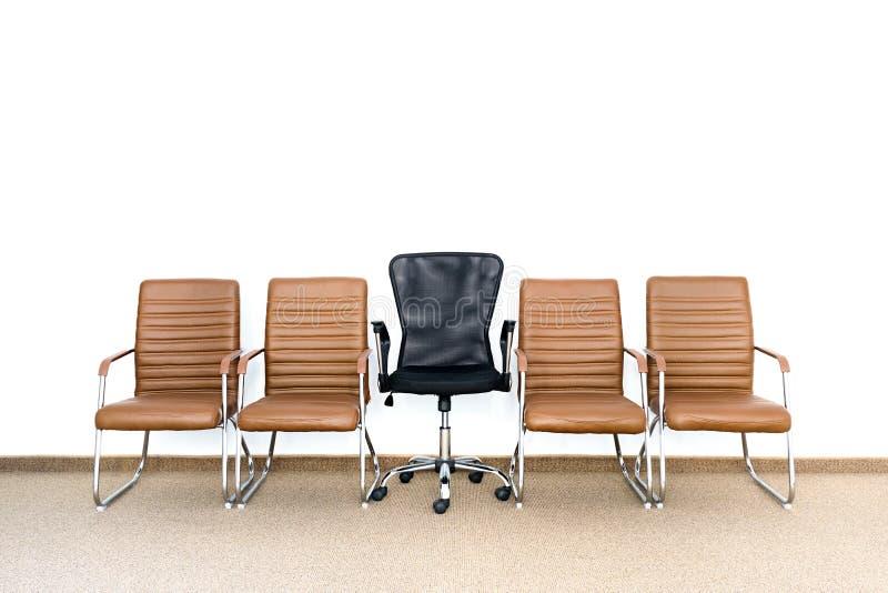 Fileira de cadeiras com a uma cadeira diferente no meio Oportunidade de trabalho imagens de stock royalty free