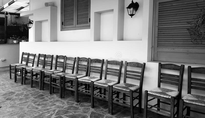 Fileira de cadeiras de madeira na parte dianteira da casa fotografia de stock