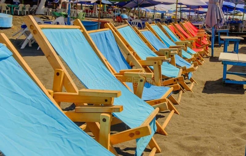Fileira de cadeiras de plataforma em uma praia morna ensolarada fotos de stock royalty free