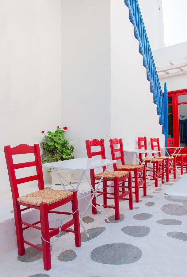 Fileira de cadeiras vermelhas em um café da rua na ilha imagens de stock