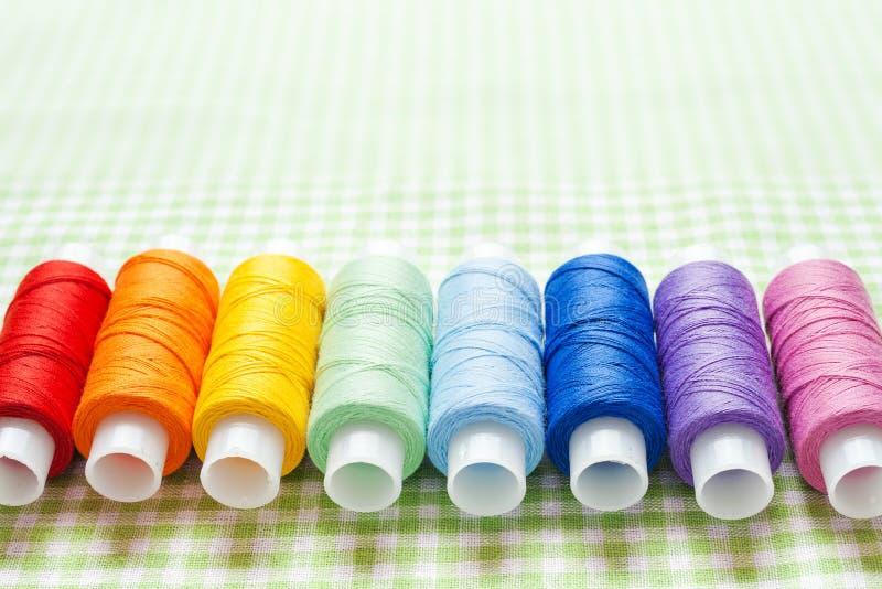 Fileira de carretéis da linha em cores do arco-íris fotografia de stock