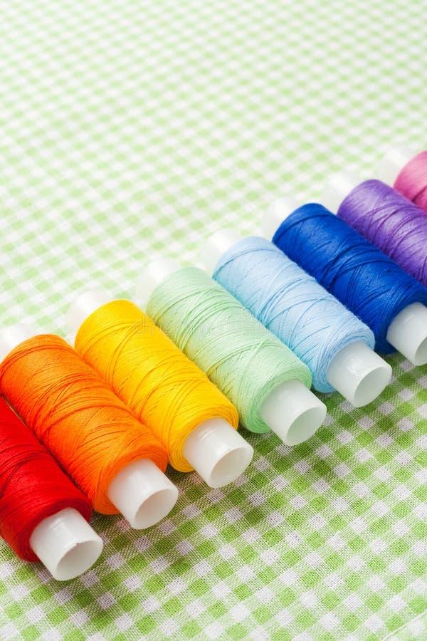 Fileira de carretéis da linha em cores do arco-íris foto de stock