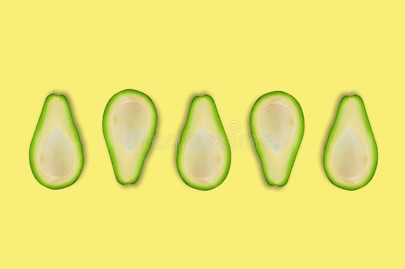 A fileira de cinco dispersou metades frescas saborosos do abacate orgânico no centro da tabela amarela na cozinha ou no mercado foto de stock royalty free
