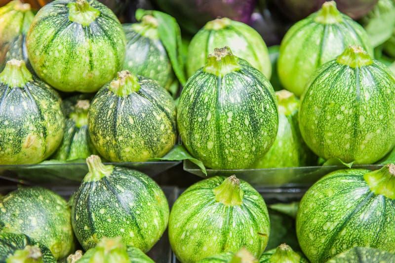 Fileira de courgettes verdes redondos na prateleira no mercado fotografia de stock