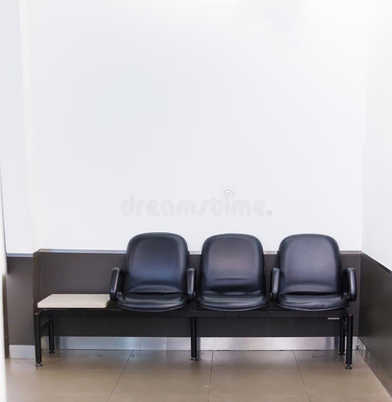 Fileira de couro preta do assento de banco no fundo branco da parede na área de espera Interior arquitetónico da casa ou do escri imagens de stock royalty free