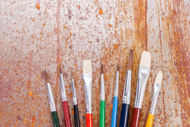 A fileira de escovas de pintura é encontrar-se misturado no fundo oxidado fotografia de stock