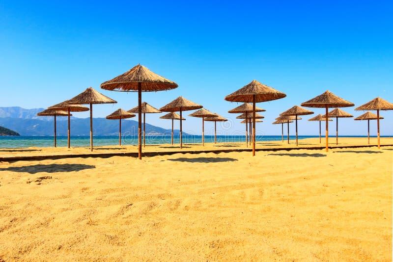 Fileira de guarda-chuvas de madeira no Sandy Beach, mar imagens de stock royalty free