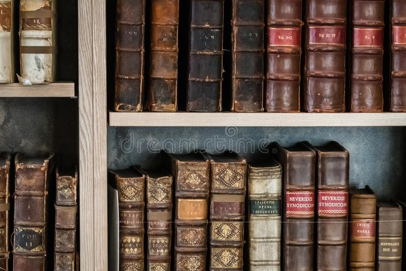 Fileira de livros antigos velhos em uma biblioteca fotos de stock