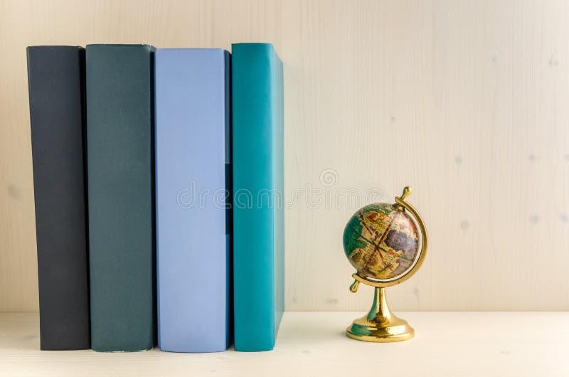 Fileira de livros coloridos e de um globo pequeno do vintage fotografia de stock royalty free