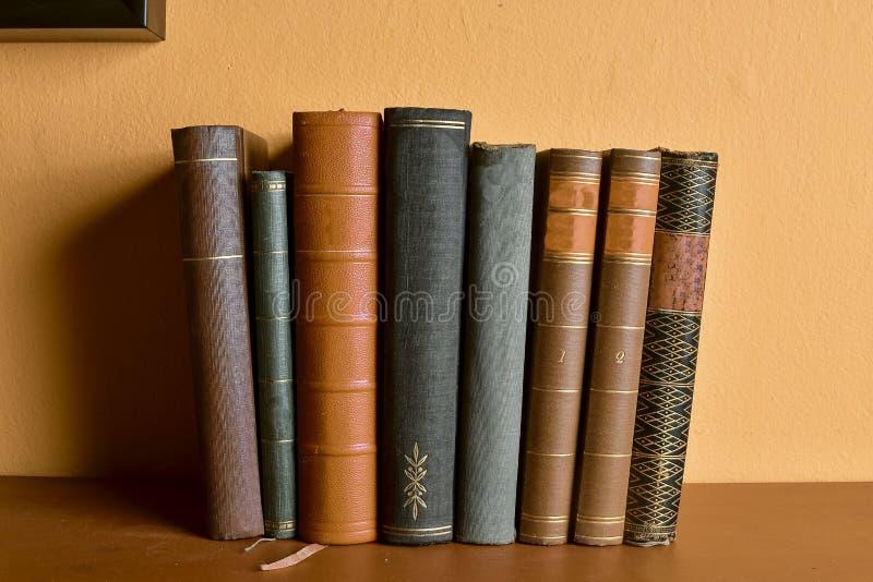 Fileira de livros encadernados velhos Livros antigos no fundo do amarelo e do clarete fotografia de stock