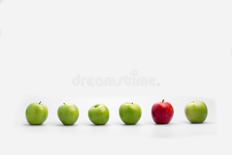 Fileira de maçãs verdes frescas com um único vermelho um fotografia de stock royalty free