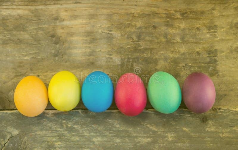 Fileira de ovos da páscoa coloridos em pranchas de madeira imagens de stock royalty free