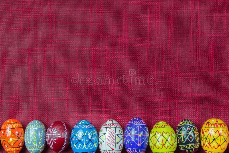 Fileira de ovos da páscoa de madeira rústicos coloridos no fundo da cor vermelha com espaço da cópia fotos de stock royalty free
