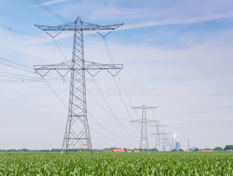Fileira de pilões e de linhas da potência em uma paisagem rural fotos de stock
