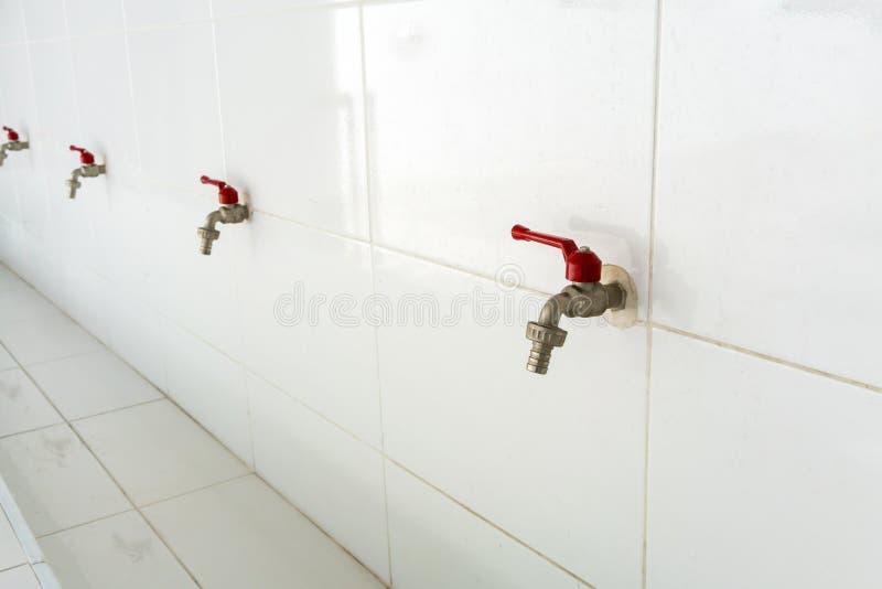 Fileira de torneiras de água vermelha contra a parede branca fotografia de stock