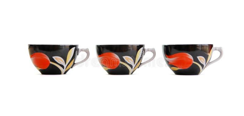 Fileira de três copos de chá preto isolados foto de stock