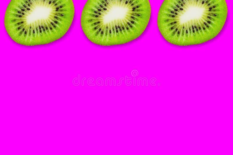 Fileira de três partes de quivi maduro fresco no fundo cor-de-rosa imagem de stock