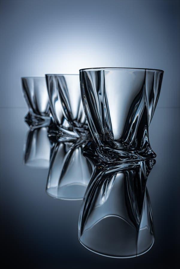 fileira de três vidros do conhaque no cinza imagem de stock
