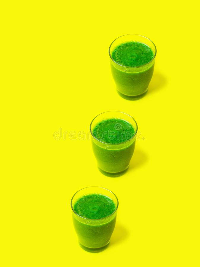 Fileira de três vidros de frutos frondosos dos vegetais dos espinafres dos batidos dos verdes no fundo amarelo ensolarado brilhan foto de stock royalty free