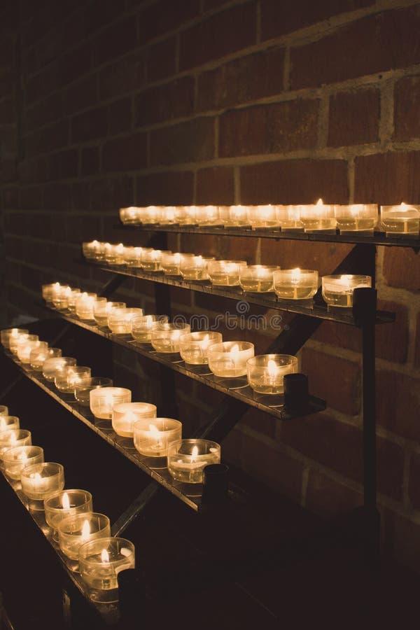 Fileira de velas de incandescência na igreja Velas com a chama no fundo escuro Conceito da f? e da religi?o Velas na igreja cat?l imagens de stock