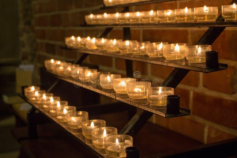 Fileira de velas de incandescência na igreja Velas com a chama no fundo escuro Conceito da f? e da religi?o Velas na igreja cat?l foto de stock royalty free