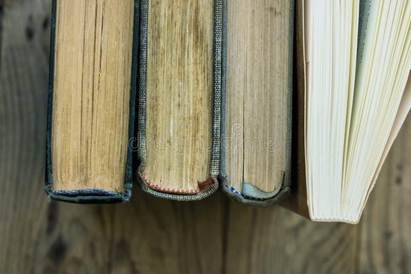 Fileira de velho e novos livros, vista superior da espinha, fundo de madeira resistido, educação, escola, aprendendo o conceito fotografia de stock