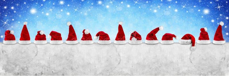 Fileira do chapéu branco vermelho do xmas do Natal de Papai Noel no concret vazio fotografia de stock