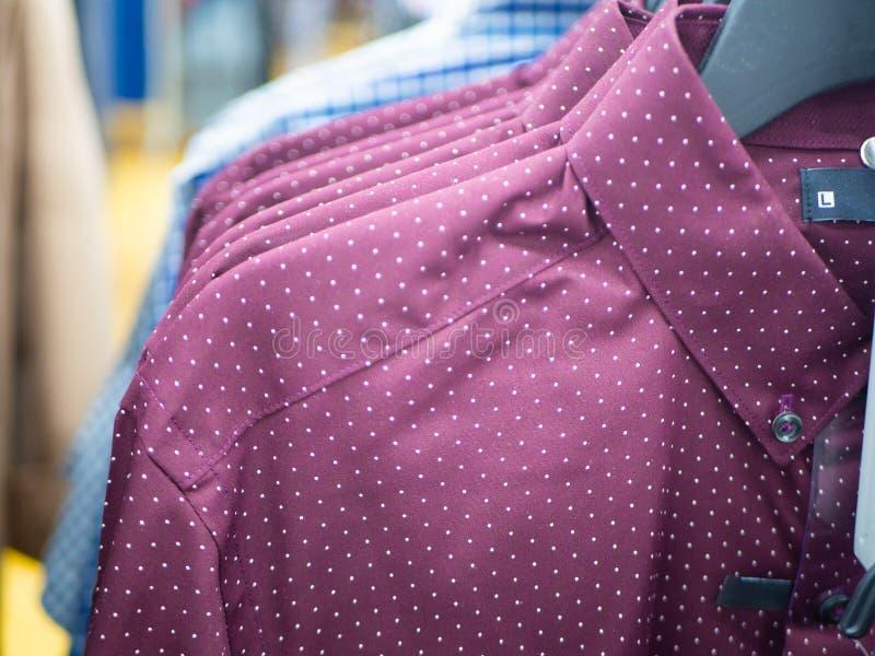 Fileira do close up de camisas do homem de Borgonha em ganchos em uma loja ou em uma sala de exposições fotografia de stock