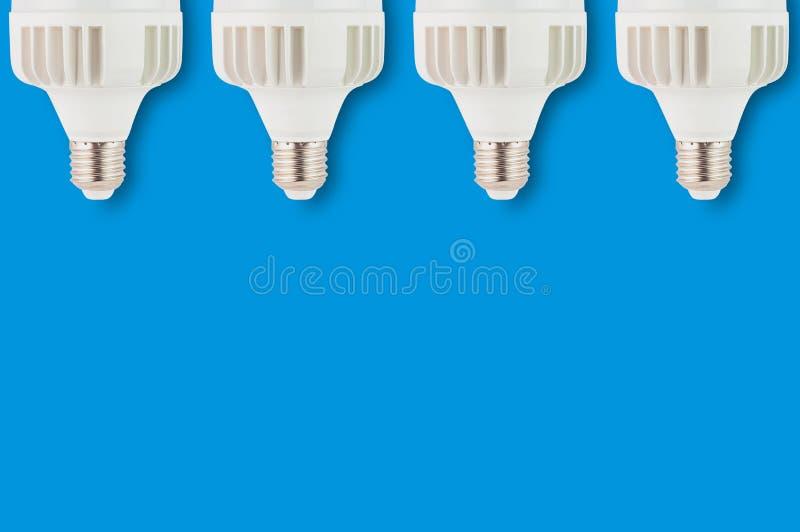 A fileira do plástico novo conduziu bulbos no fundo azul com espaço da cópia para seu texto Economia e economia ou conceito verde fotos de stock