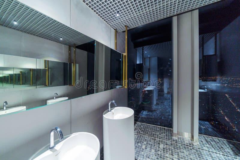 Fileira do toalete cerâmico branco moderno da bacia de lavagem em público com fundo da arquitetura da cidade, o toalete no restau imagem de stock royalty free